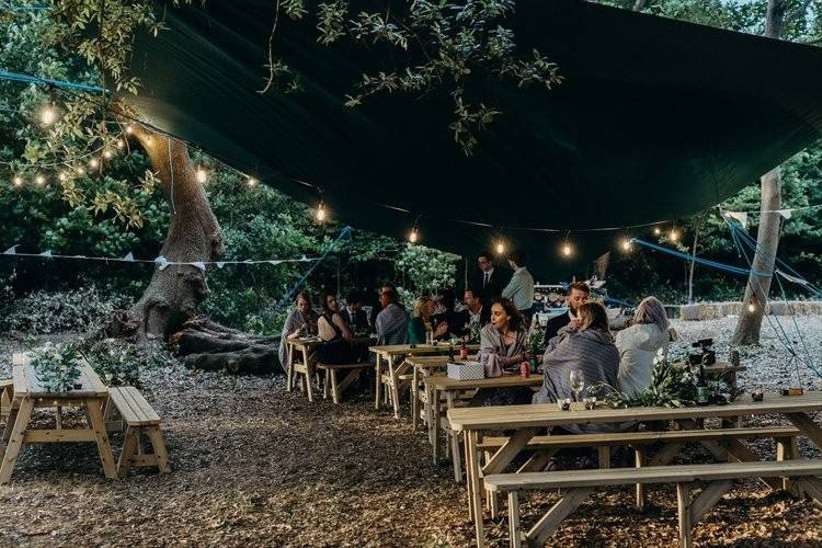Wedding guests sitting on benches under a canopy and fairy lights