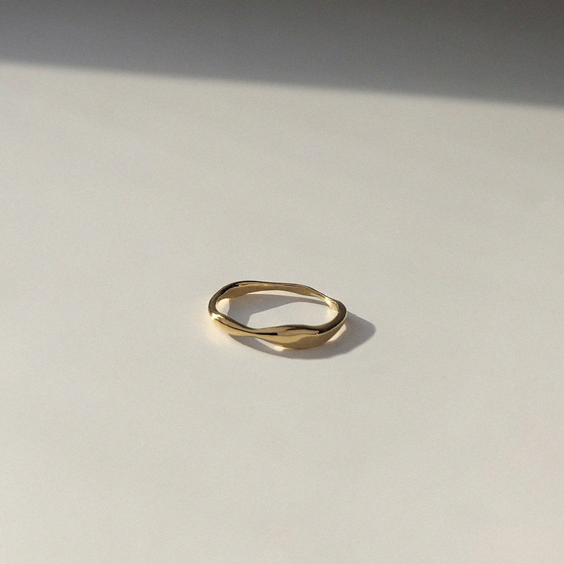 Ripple effect gold ring on a plain grey surface