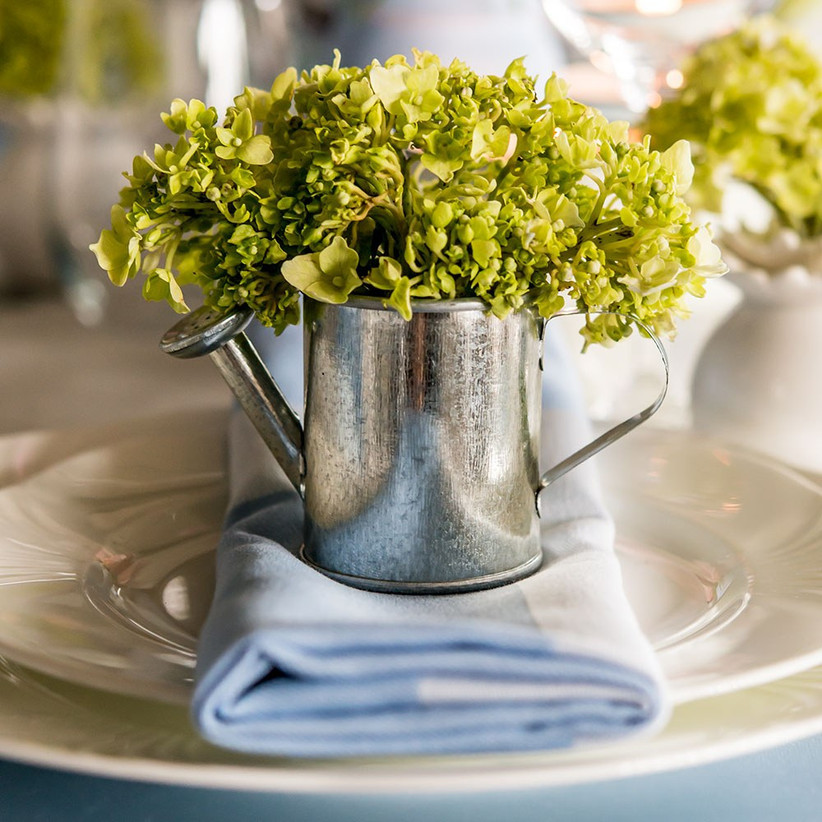 Miniature watering can with green flowers