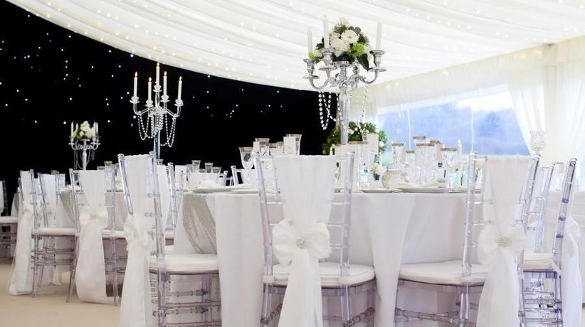 clear-chairs-decorated-with-white-sashes