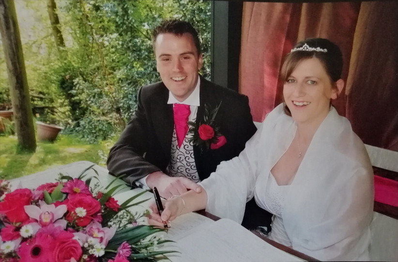 White newlywed couple seated and smiling while signing the marriage register in front on a pink and white floral display