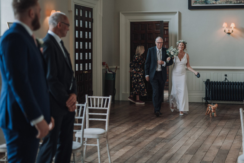 Katherine walking into the ceremony room with her father and her pet dog