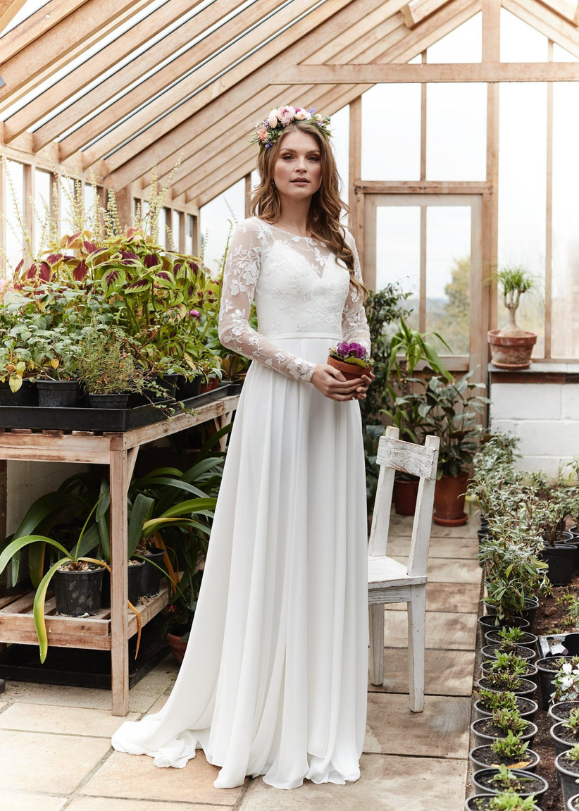 Model with a flower crown wearing a lace long sleeved wedding dress