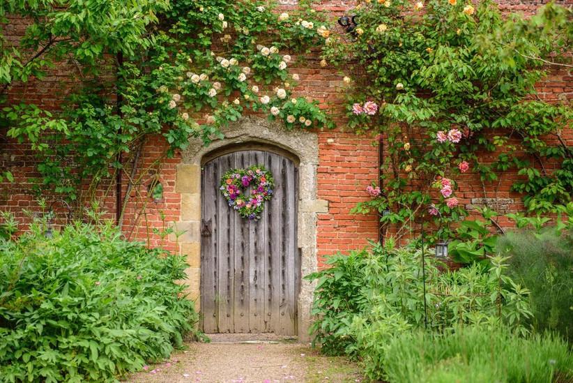 Wooden door in a garden with a floral heart wreath