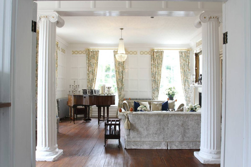 An elegant living area with a sofa, long curtains and a grand piano