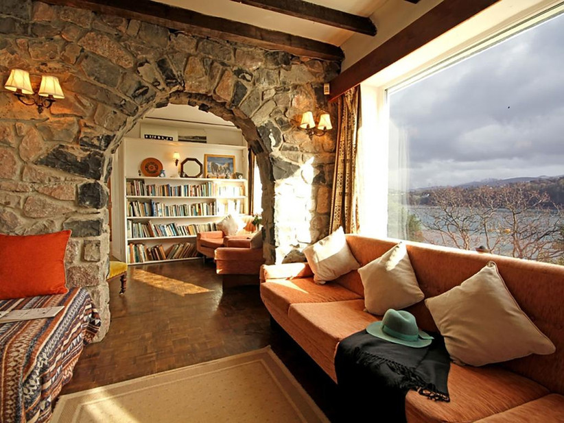 Sofa with view of the sea next to an exposed stone wall and bookcase