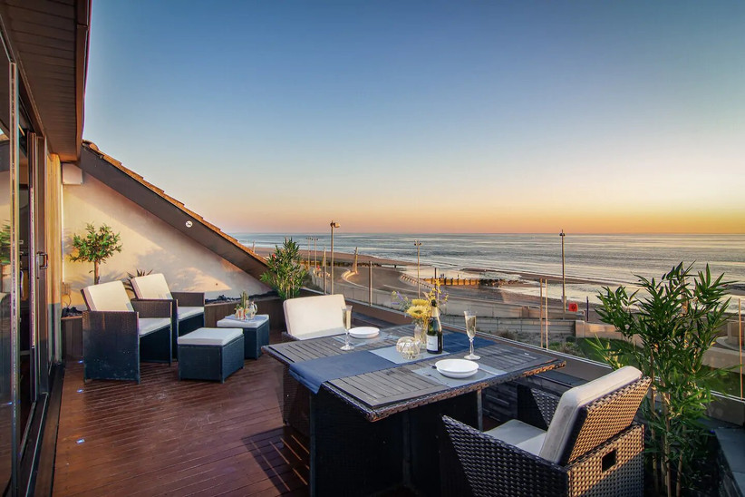Balcony with tables and chairs overlooking the sea at sunset