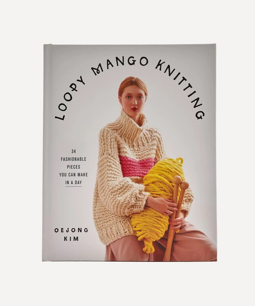 Loopy Mango Knitting book with a white woman with red hair in a wooly jumper on the front holding a giant ball of yellow wool and oversized wooden knitting needles