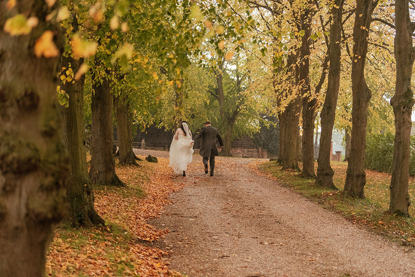 Becky and Ben walking down a tree-lined avenue