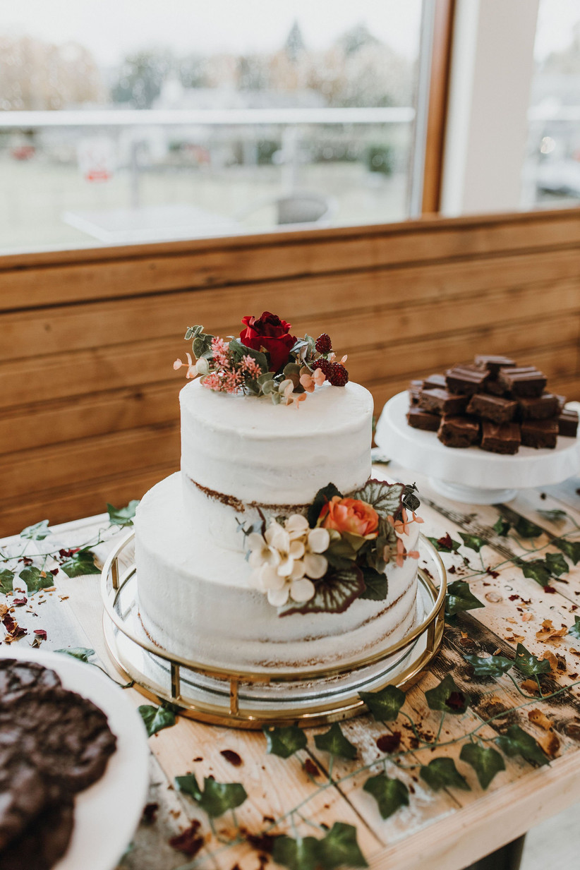 A white wedding cake next to a plate of brownies