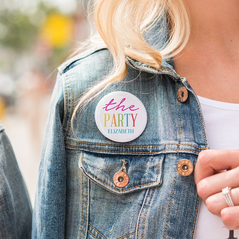 Girl wearing a badge that says the party Elizabeth