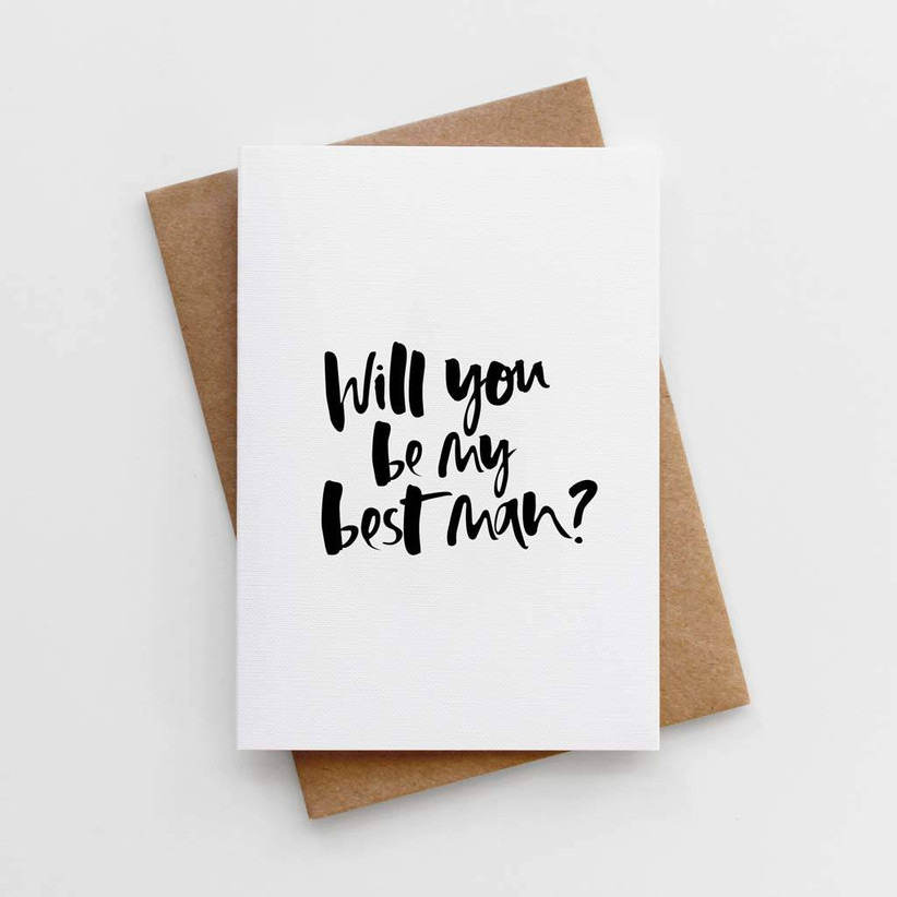 White card with a will you be my best man message written in black brushstroke lettering