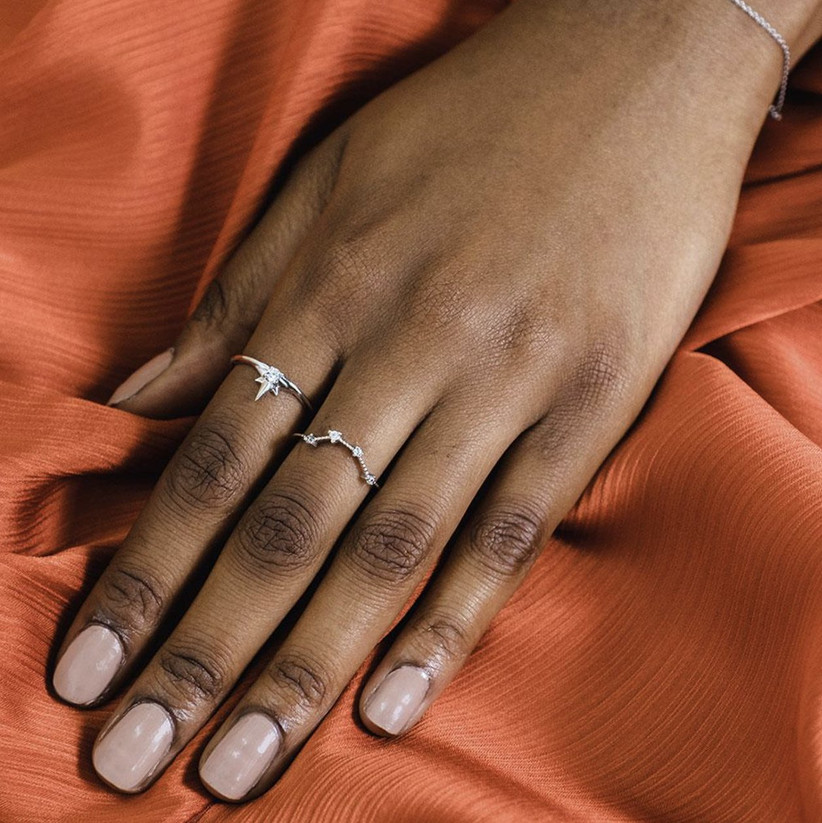 Close up of woman's hand wearing a white gold star shaped ring with a diamond at its centre on her first finger and a constellation style studded diamond ring on her middle finger against an orange fabric background
