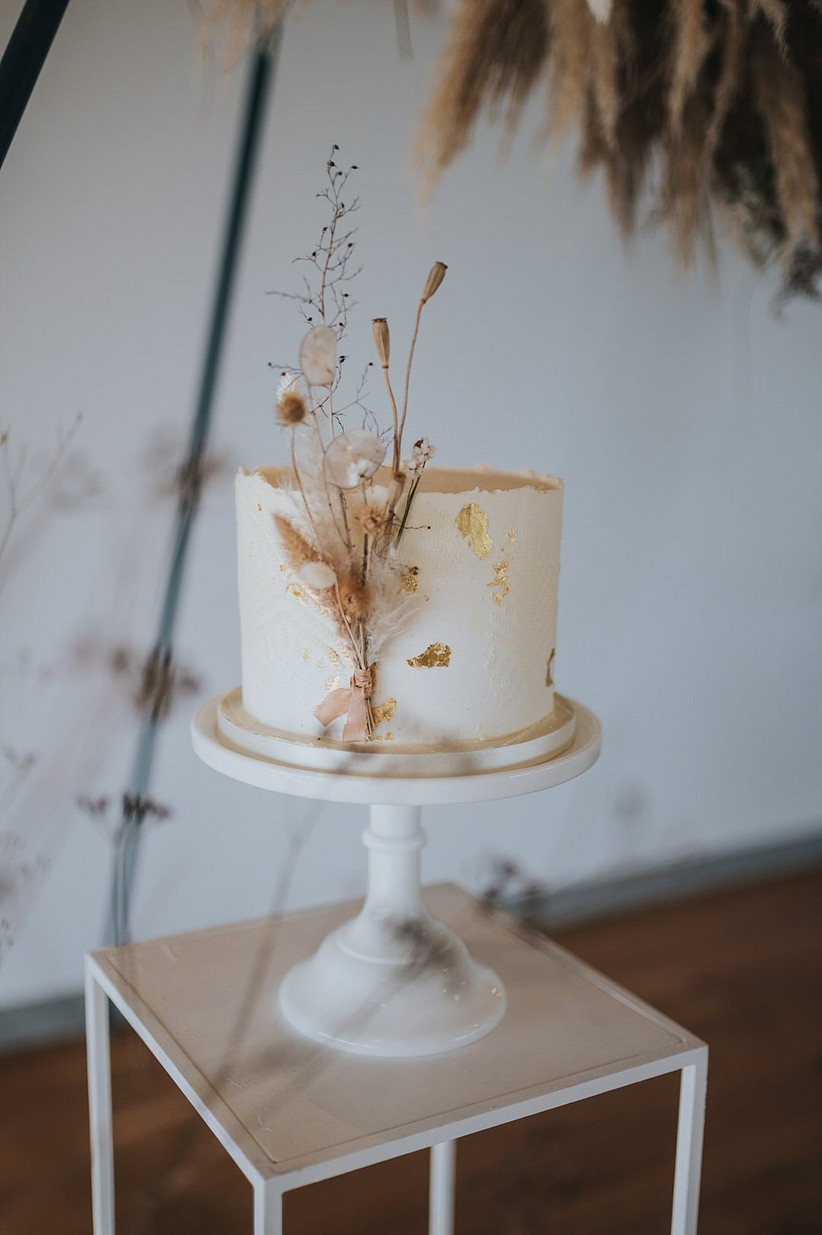 Single tier rustic wedding cake with neutral dried foliage