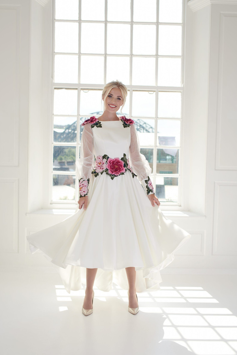 Model wearing a sheer long sleeved wedding dress with pink roses