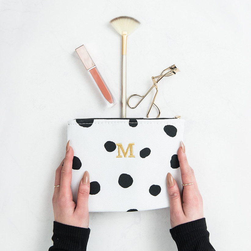 Woman holding black and white polka dot makeup pouch with a golden M embroidered onto the centre and makeup spilling out