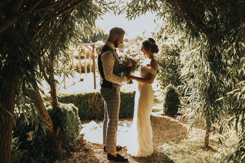 Bride and groom under a grass archway