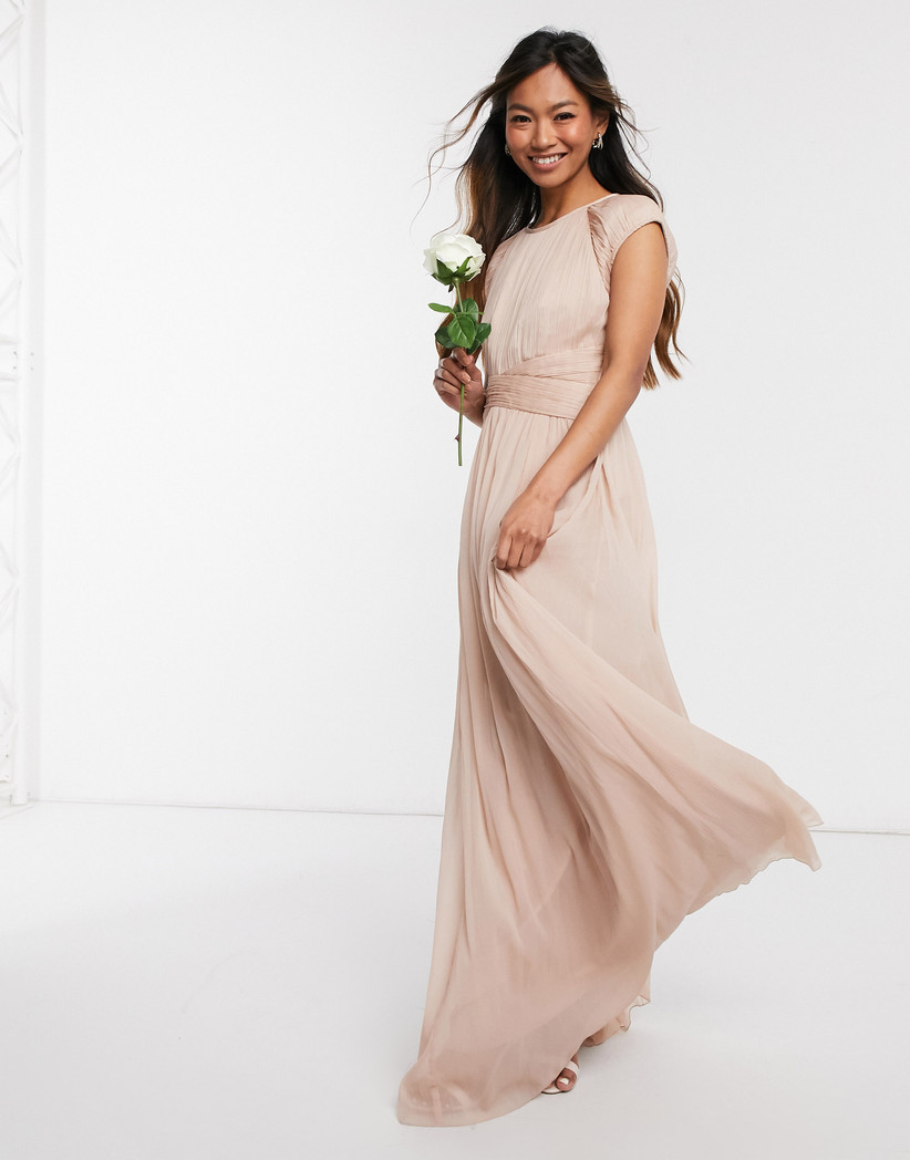 Girl wearing a cream maxi dress holding a white rose