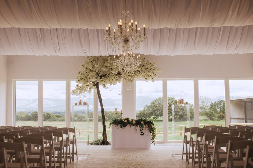 Wedding ceremony with white floral tree and views of the countryside