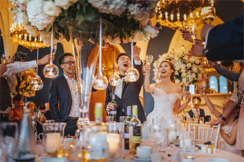 Bride, groom and wedding guests cheers around a dinging table