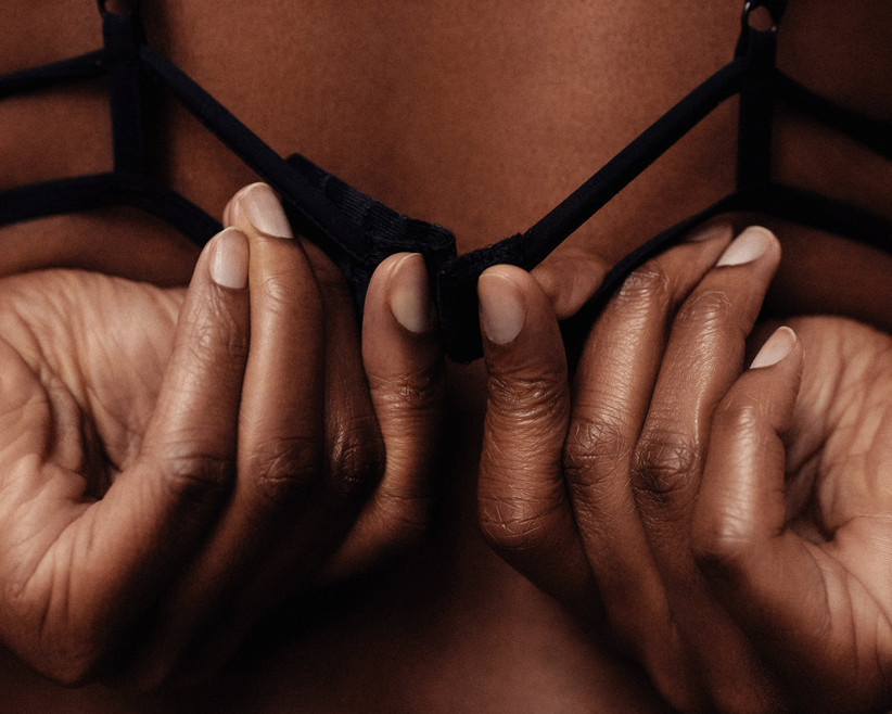 Woman doing up clasp of a black bra