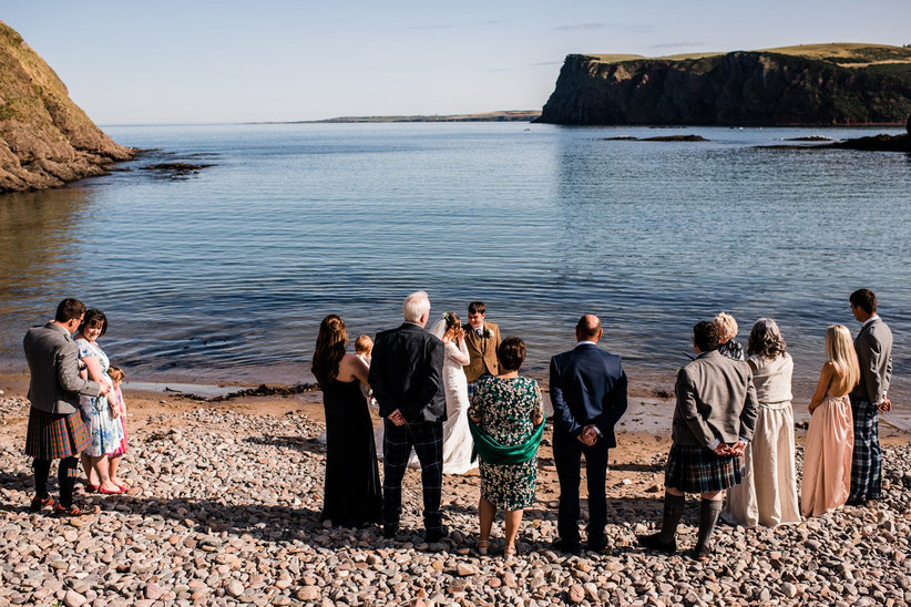 Caitlin, Stephen and their ten wedding guests on the beach