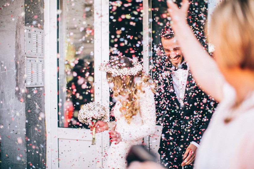 Photo of just married couple. Guests are throwing confetti in the air.