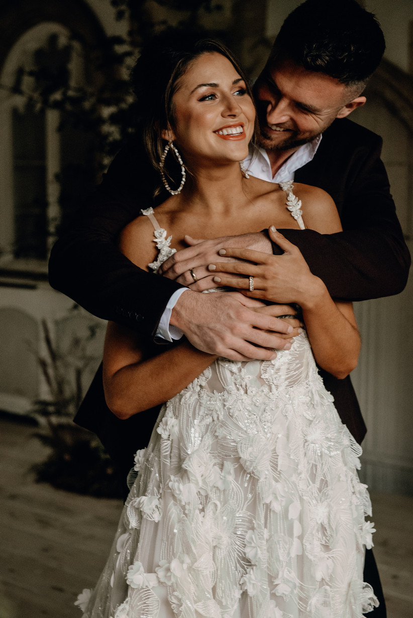 Bride with large earrings laughing whilst being held by a groom