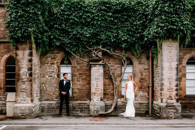 Bride and groom pictured against a brick wall