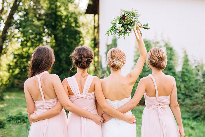 Bride and three bridesmaids in pink, shot from behind
