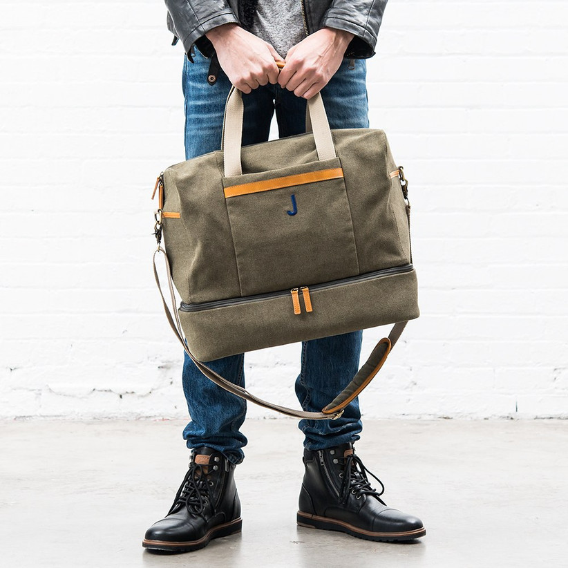 Man in blue jeans holding a camel coloured canvas and leather weekend bag in front of him with yellow detailing and a J initial in blue