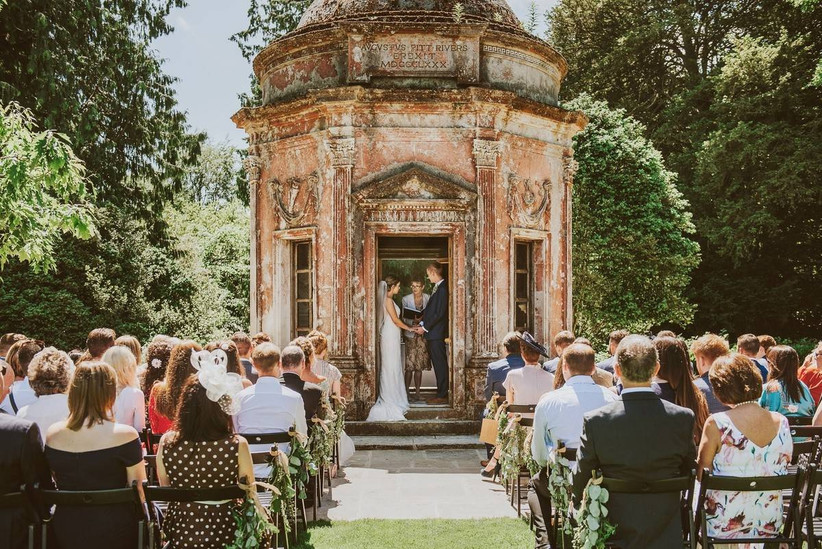 Bride and groom marry in a stone pavilion