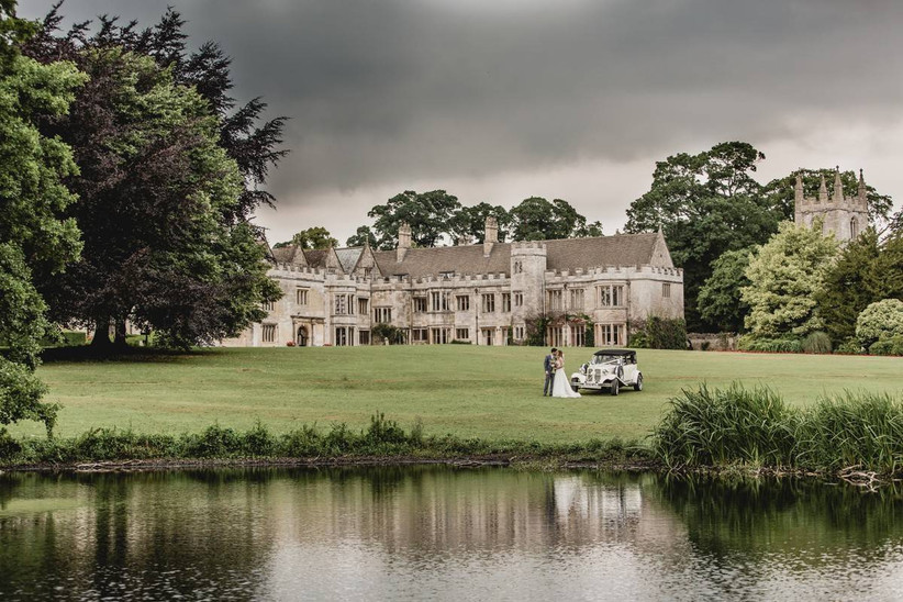 Couple standing next to a vintage car outside a large manor house
