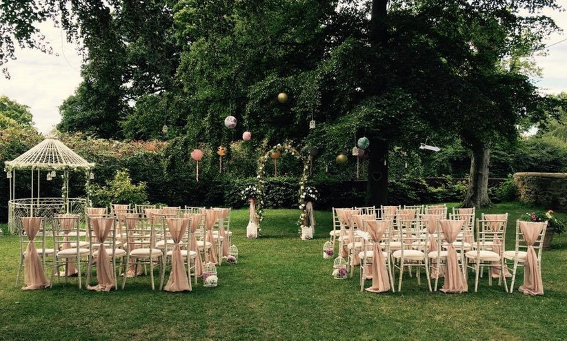 Outside ceremony with white chairs and lantern decorations