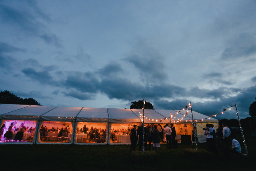 Wedding marquee at dusk strung with fairy lights