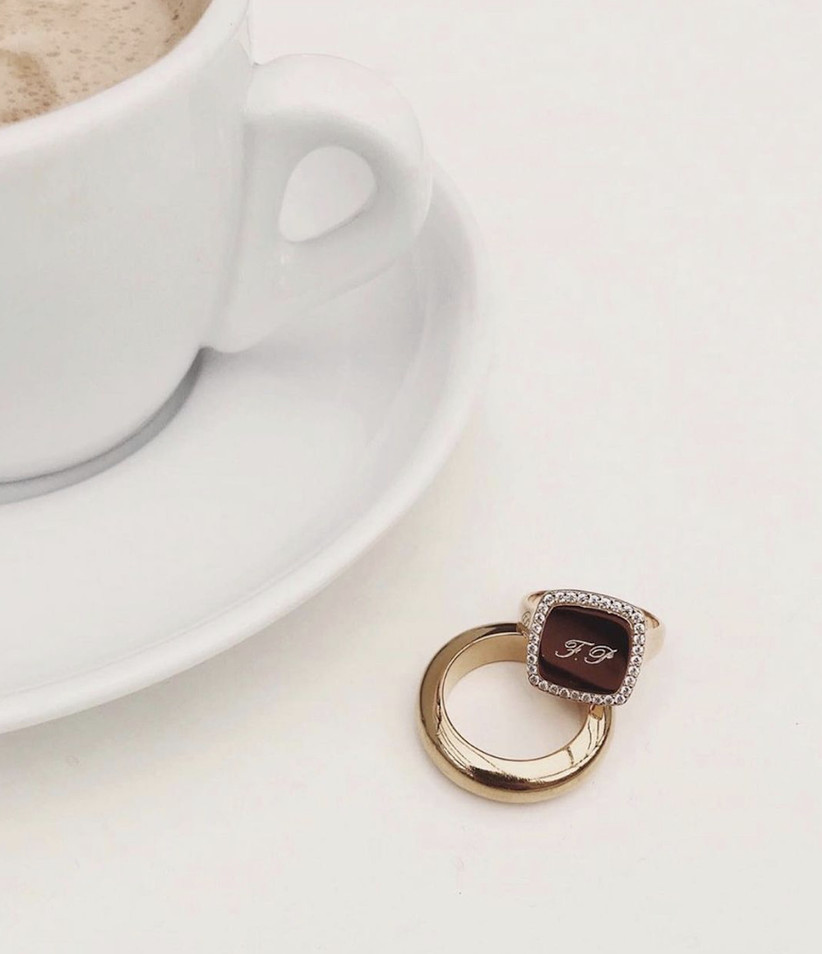A plain shiny gold band with an engraved gold signet ring with a border of pave diamonds balanced on top of it on a white surface next to a white teacup and sauce
