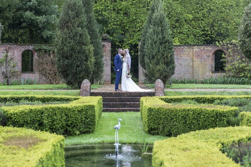 Bride and groom kissing in the gardens of Hertfordshire wedding venue Burloes Hall