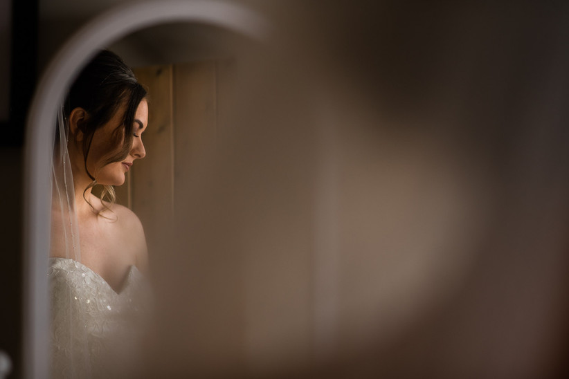Caitlin in a wedding dress and veil reflected in a mirror