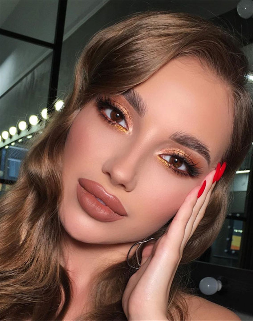 Girl with gold glitter eyeshadow and brown lipstick
