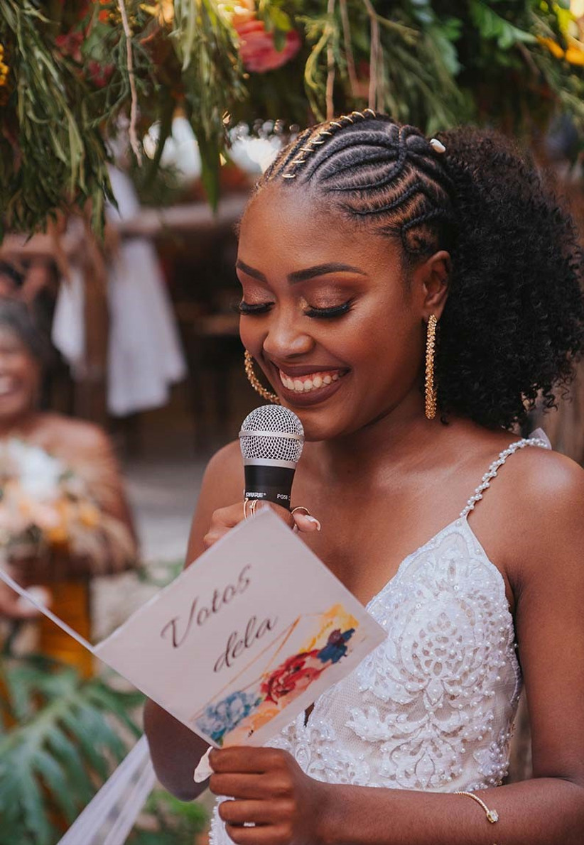 Bride making a speech holding a microphone and card