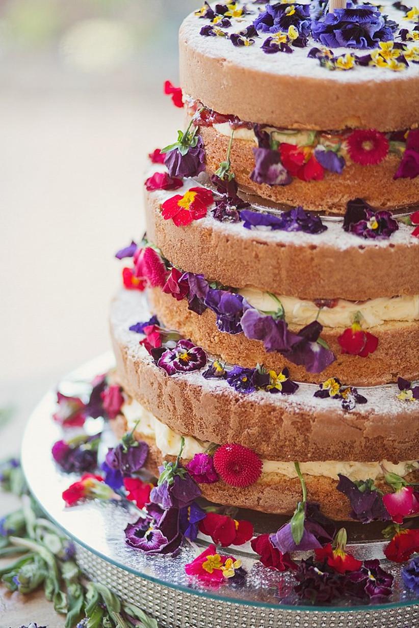 Naked victoria sponge rustic wedding cake with edible flowers