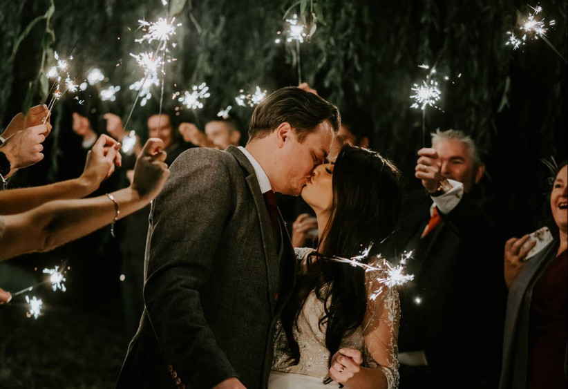 Bride and groom kissing with sparklers on their wedding day