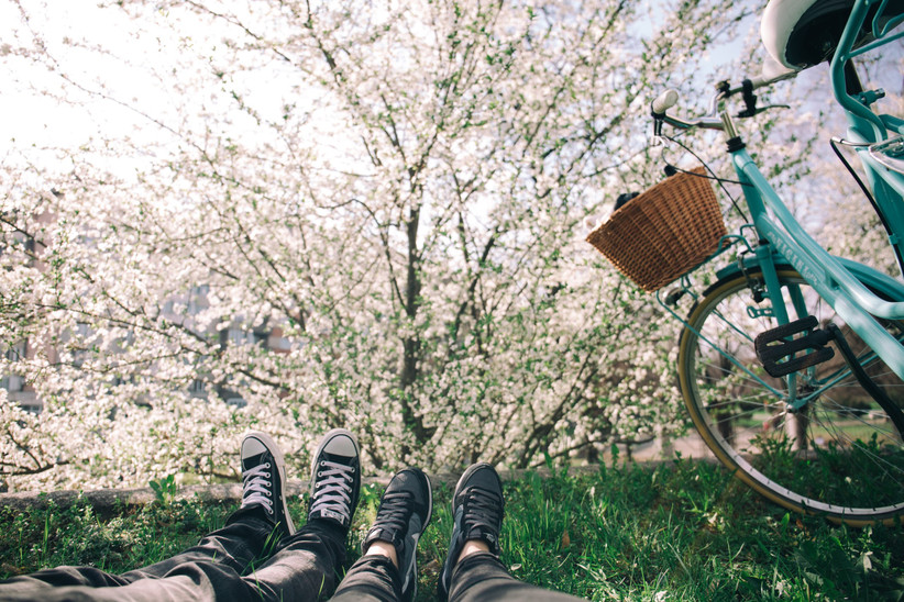 Shot of couple's legs lying on grass with both wearing trainers next to a blue bike