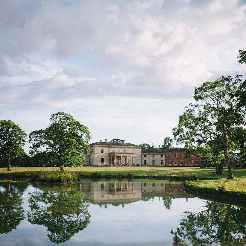 Exterior of country house Stubton Hall surrounded by manicured gardens and with a tranquil lake in front
