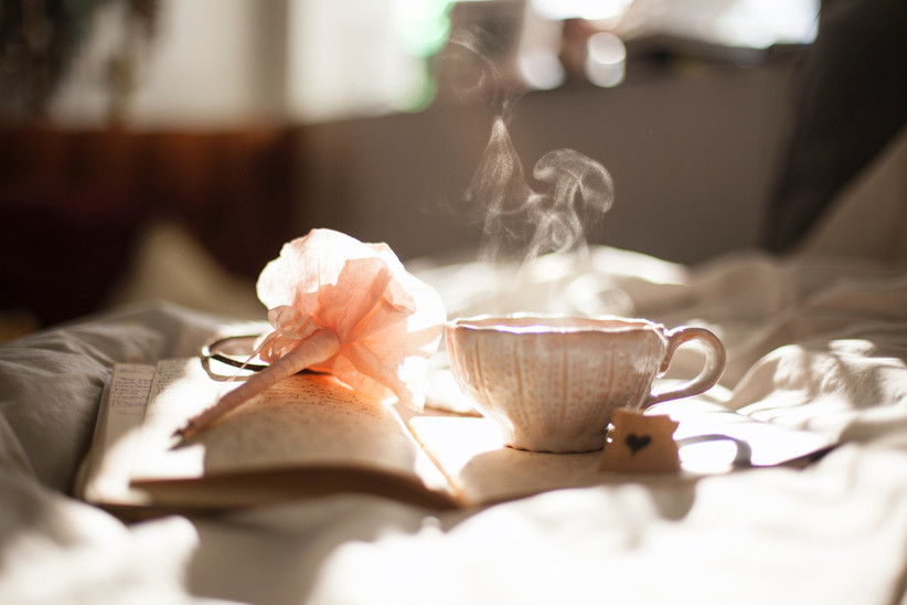 Open notebook with writing in it with a steaming teacup and pale pink pen on top of it