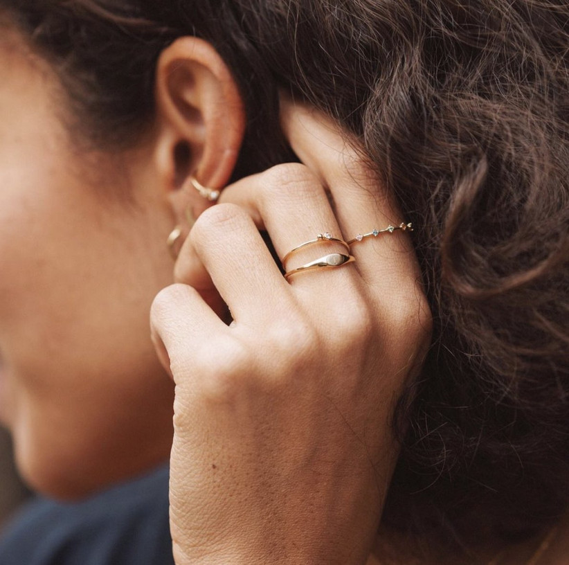 Close up of woman touching her ear wearing a selection of dainty rings with a slim engraved signet ring on her middle finger