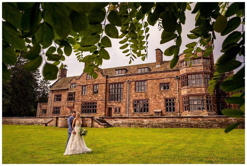 Bride and groom stand outside a country house