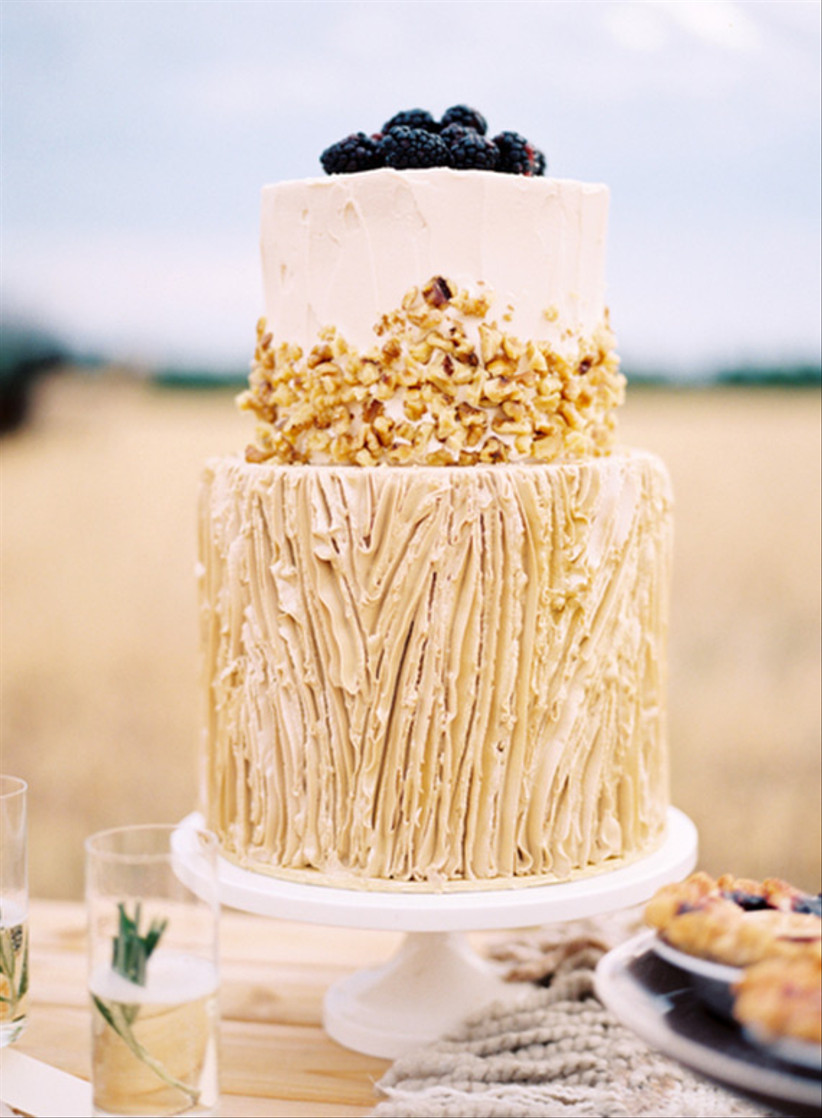 Two tiered sand coloured rustic wedding cake with texture and chopped nuts