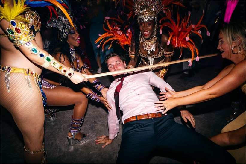 Man doing the limbo surrounded by girls in carnival outfits