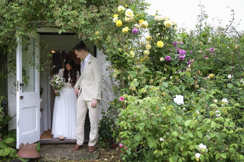 Bride and groom walking out of a farm door holding hands surrounded by flowers
